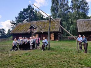 Miniatura zdjęcia: grupa seniorów stoi przy chacie w skansenie