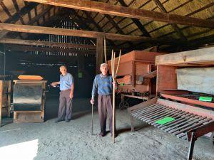 Miniatura zdjęcia: dwóch panów w stodole ogląda stare maszyny